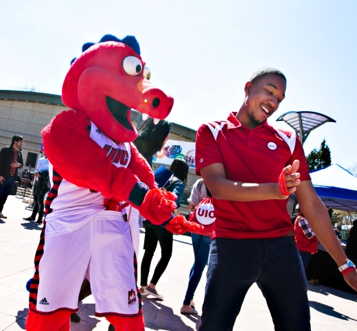 A student dancing with Sparky the Dragon, the UIC mascot